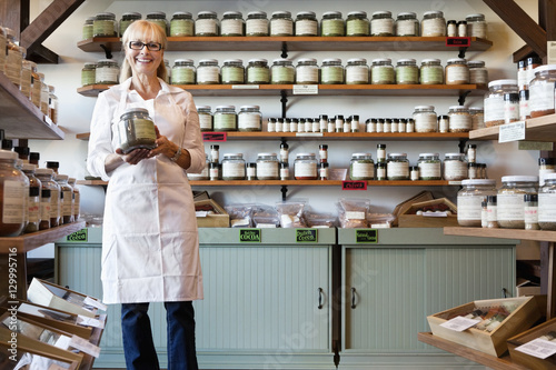 Photo Portrait of a happy senior merchant standing with spice jar in store