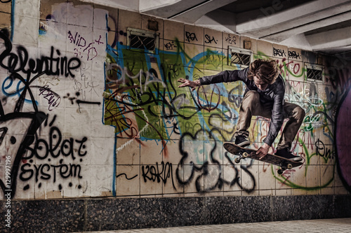 Skateboarder performing grab on graffiti wall background © 27mistral