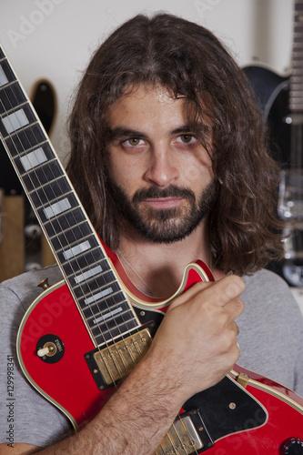Spoed Foto op Canvas Muziekwinkel Portrait of serious young musician holding guitar
