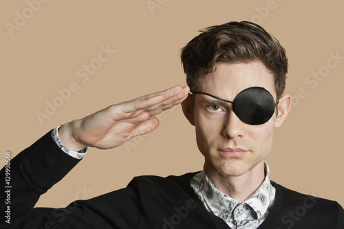 Fotografie, Tablou  Portrait of a man wearing eye patch saluting over colored background