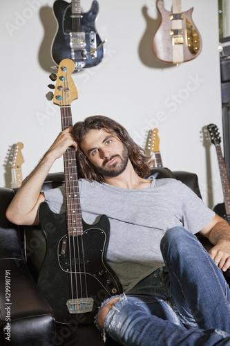 Spoed Foto op Canvas Muziekwinkel Portrait of man sitting on couch holding a guitar
