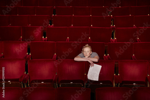 Photo  Thoughtful young woman sitting in theatre stall with script