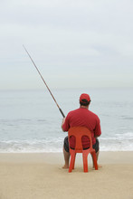 Rear View Of A Man In Red Tshirt Sitting On Red Plastic Chair And Fishing At Beach