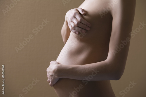 6a792ac90cf Midsection side view of naked pregnant woman covering breast and abdomen on  colored background