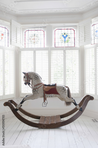 Valokuvatapetti Antique rocking horse in bay window with stained glass
