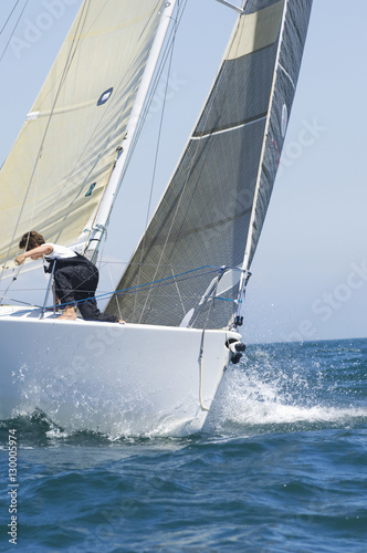 Poster Zeilen Crew member on a cropped yacht competing in team sailing event