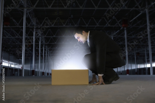 Photo  Full length side view of businessman looking at glowing box in empty warehouse