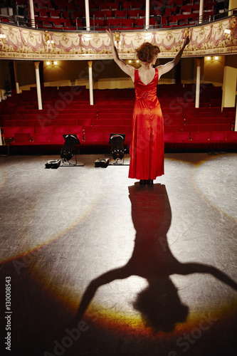 Photo  Full length rear view of a woman in red gown standing on stage floor