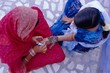 Woman's hand being decorated with henna design, Rajasthan, India