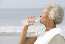 Side View Of Senior Woman Drinking Water With A Towel Over Her Shoulder On Beach