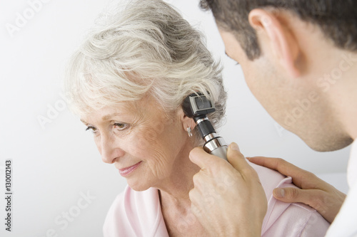 Photo Male doctor examining patient's ear using otoscope at clinic
