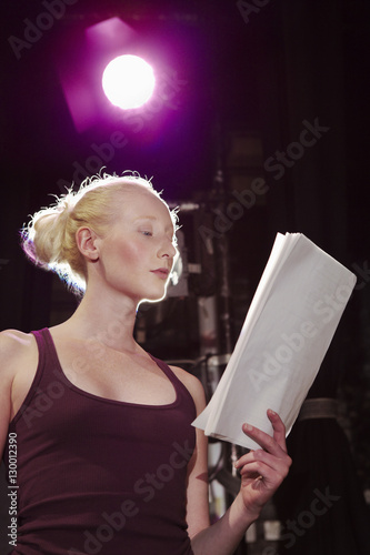 Low angle view of a young woman reading script on stage Canvas Print