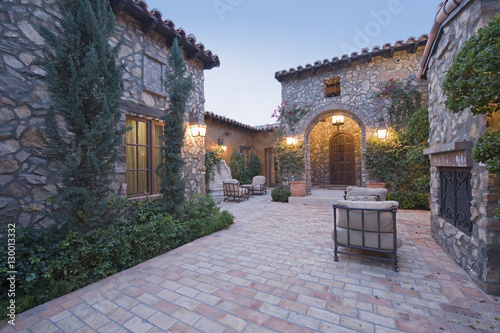 Fotografia, Obraz Exterior of stone houses with chairs in courtyard