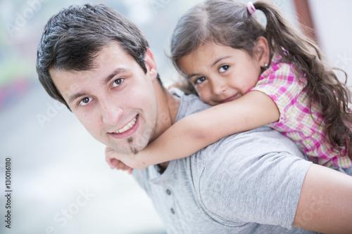 Fotografie, Obraz  Side view portrait of smiling man piggybacking little daughter at home