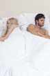 Angry young couple avoiding each other in bed