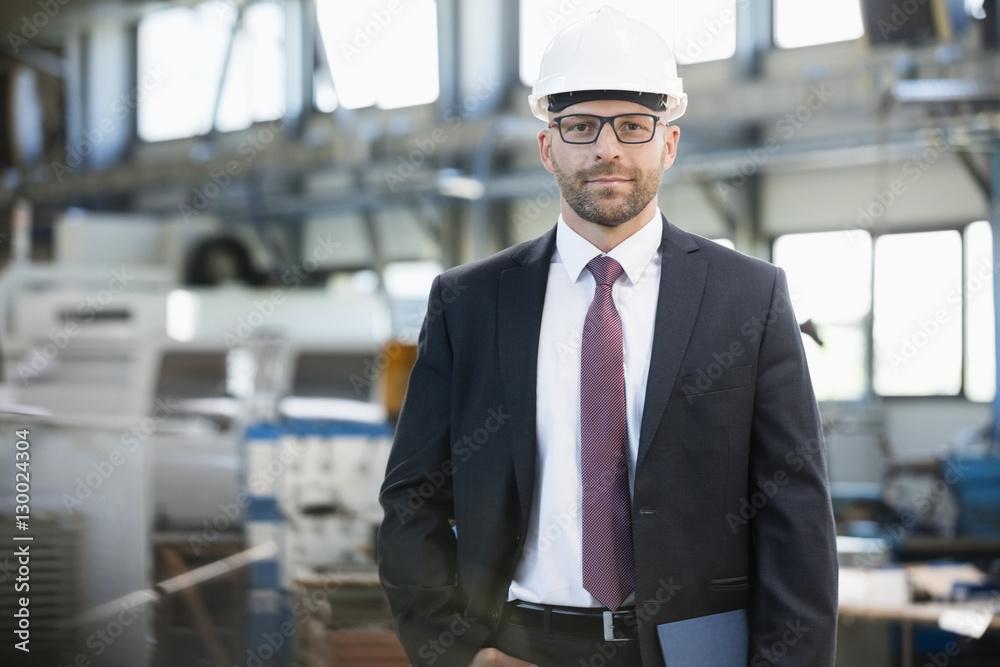 Fototapeta Portrait of confident mid adult businessman wearing hardhat in metal industry