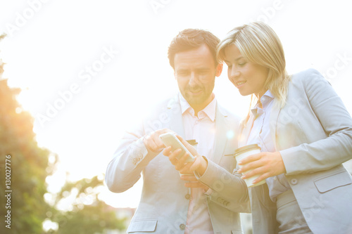 Valokuva  Business couple conversing while using cell phone on sunny day