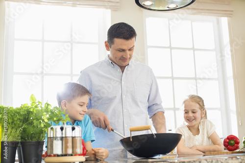 Fotografie, Obraz  Children looking at father preparing food in kitchen