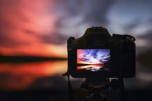 Camera Capturing Sunset. Photo...