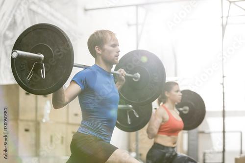 Fotografie, Obraz  Man and woman lifting barbells in crossfit gym