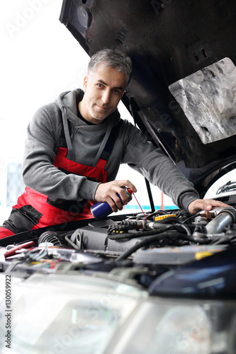 Fotografía  Mechanik samochodowy czyści i smaruje śruby pod maską samochodu