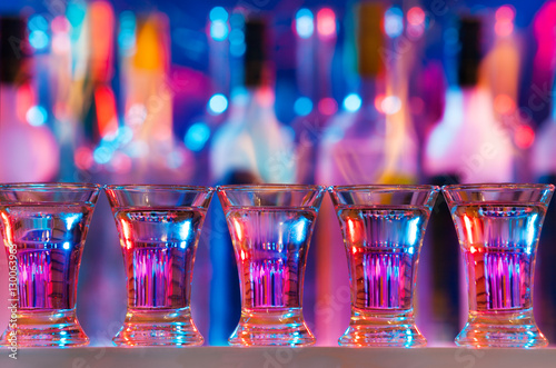 Fotografie, Obraz  Five burning drinks in shot glasses on bar counter
