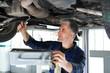 Wymiana oleju silnikowego. Mechanik samochodowy wymienia olej silnikowy w warsztacie samochodowym.
