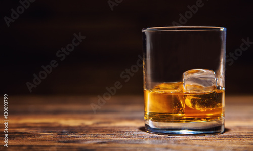 Poster Alcohol Glass of whiskey with ice cubes served on wood
