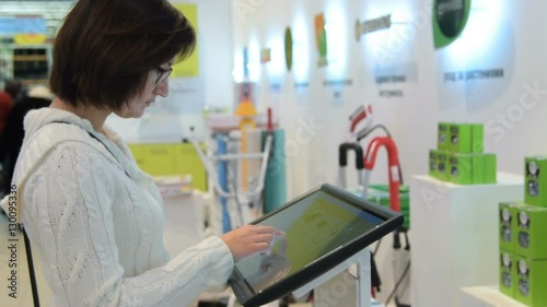 Woman choosing goods in the electronic touchscreen catalog in the hypermarket