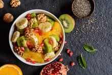 Healthy Fruit Salad Made Of Orange, Kiwi, Banana, Walnuts, Pomegranate And Chia Seeds