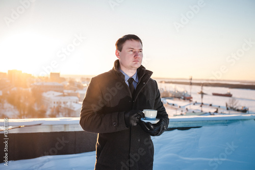 Photo  Young man drinking coffee on the roof of the building in winter.