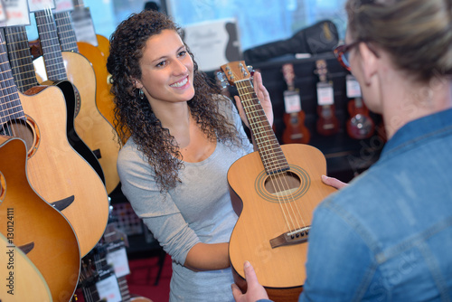 Deurstickers Muziekwinkel Woman passing guitar to customer