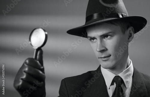 Foto  Young vintage detective holding a magnifying glass