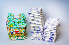 Compare Reusable Cloth Diapers With Pile Of Disposable Diapers