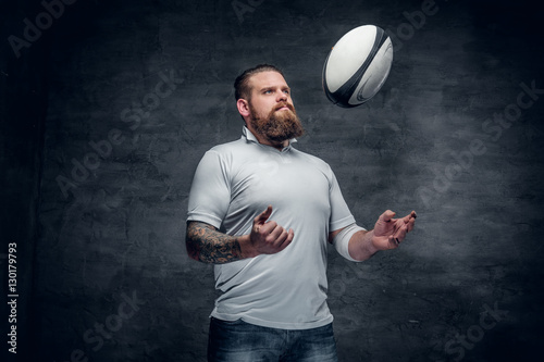 Plakat Brodaty rugby gracz łapie piłkę do gry.