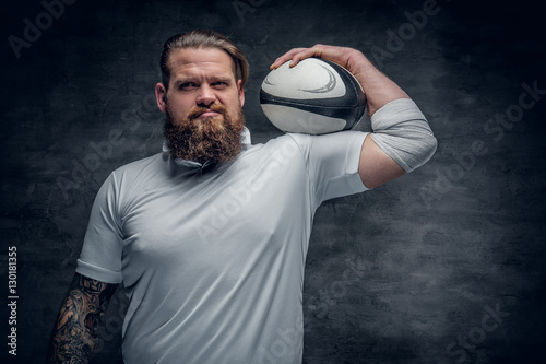 Bearded rugby player holds game ball.