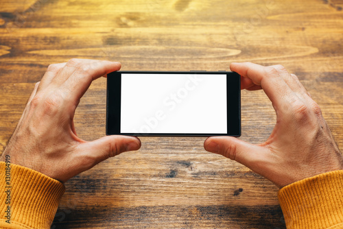 Man using smart phone in horizontal landscape orientation