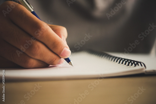 Man hand with pen writing on notebook. Canvas Print