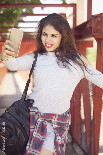 Poster Gypsy Beautiful young woman taking a self portrait with mobile phone outdoors