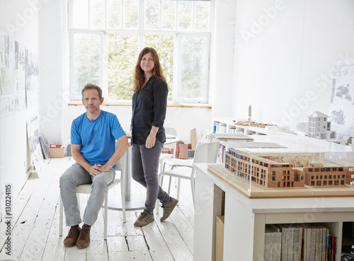 A modern office with white walls and floors. A man sitting and a woman standing. An architectural model on a table.