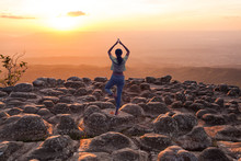A Woman Practices Yoga On Silhouette Of Sunset And Light Flare At The Mountain Named Lan Hin Poom At Phu Hin Rong Kla National Park, Phitsanulok Province, Thailand