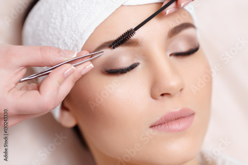 Canvas Print Beautiful young woman gets eyebrow correction procedure