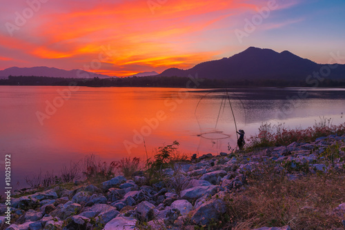 View of Mae Moei reservoir with a fisherman dipping his dip fishing net during twilight time of the day.