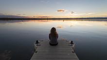 Girl Sitting On Dock Sunset