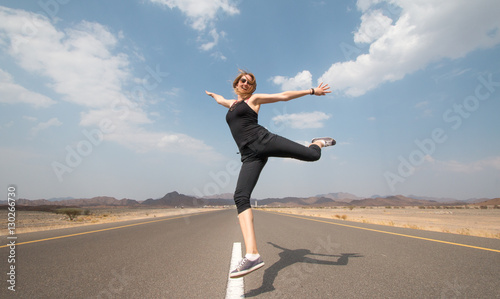 Young happy woman on an empty road in Oman desert. Tableau sur Toile