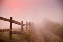 Foggy Rural Scene. Fence And Dirt Road At Misty Morning
