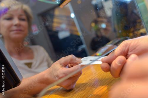 Fotografía  Customer taking ticket from under glass hatch