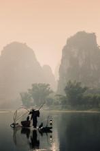 Silhouette Of A Cormorant Fisherman Paddling A Lantern Lit Bamboo Raft At Sunrise On The Li River, China