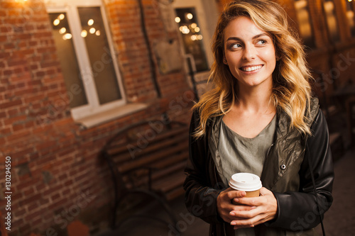 Fényképezés Young attractive woman with coffee to go outdoors on street