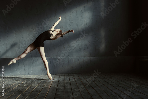 Fotografie, Obraz  Skillful young ballet dancer acting in the black colored room